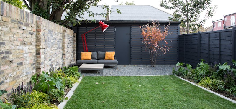 Grey gravel under a grey seating area in front of a dark grey shed.