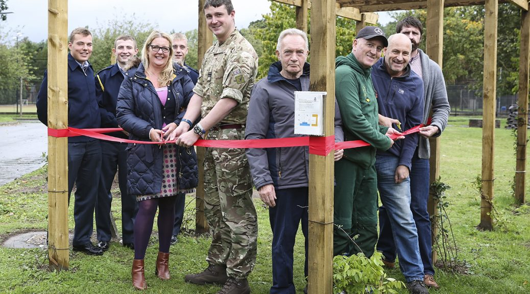 people standing in garden with a red ribbon to be cut