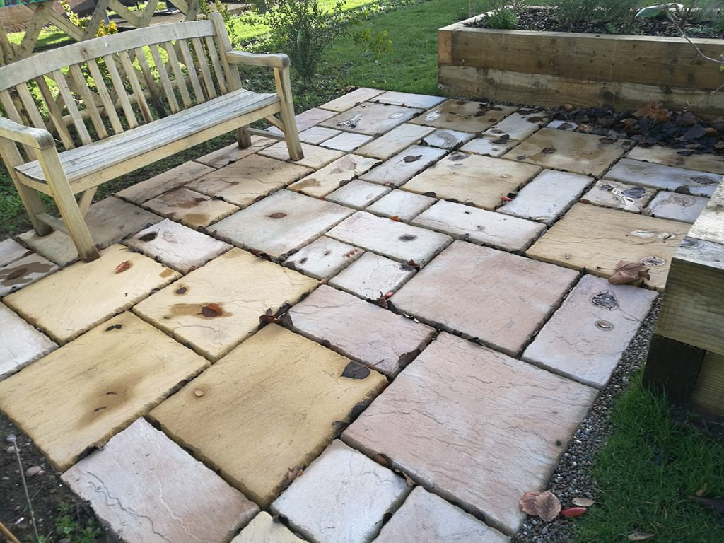Paving slabs with benches set onto them to create patio areas.