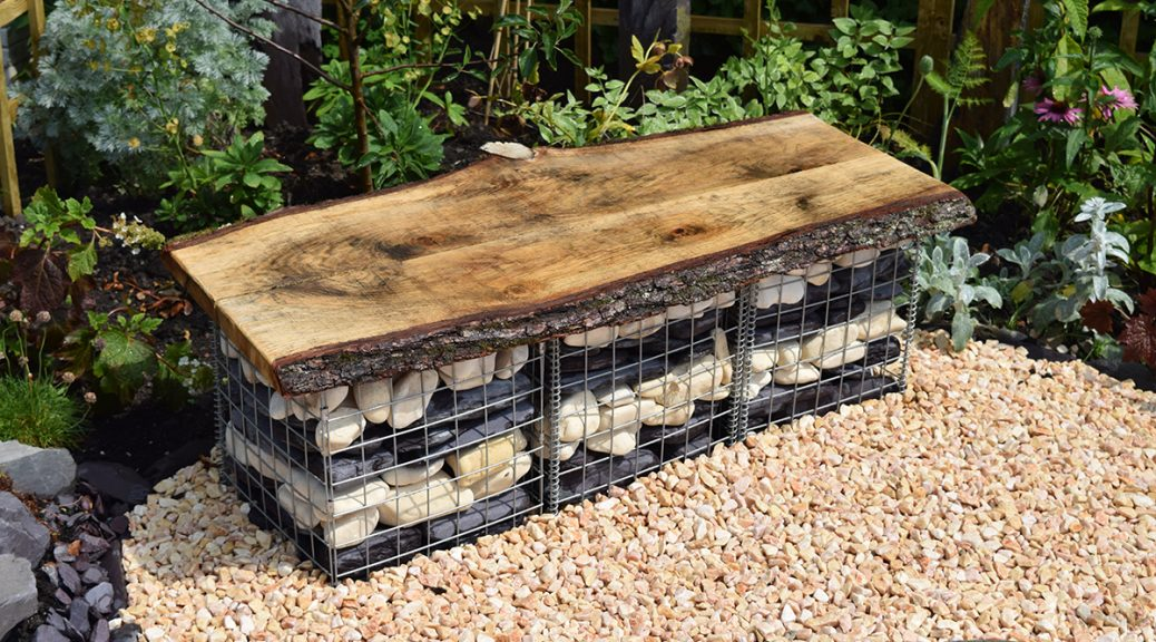 Steel basket made into a seat filled with cream cobbles and plum slate paddlestones in a layered effect.