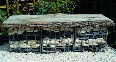 Gabion basket made from steel with layers of cream cobbles and plum slate paddlestones filling it.