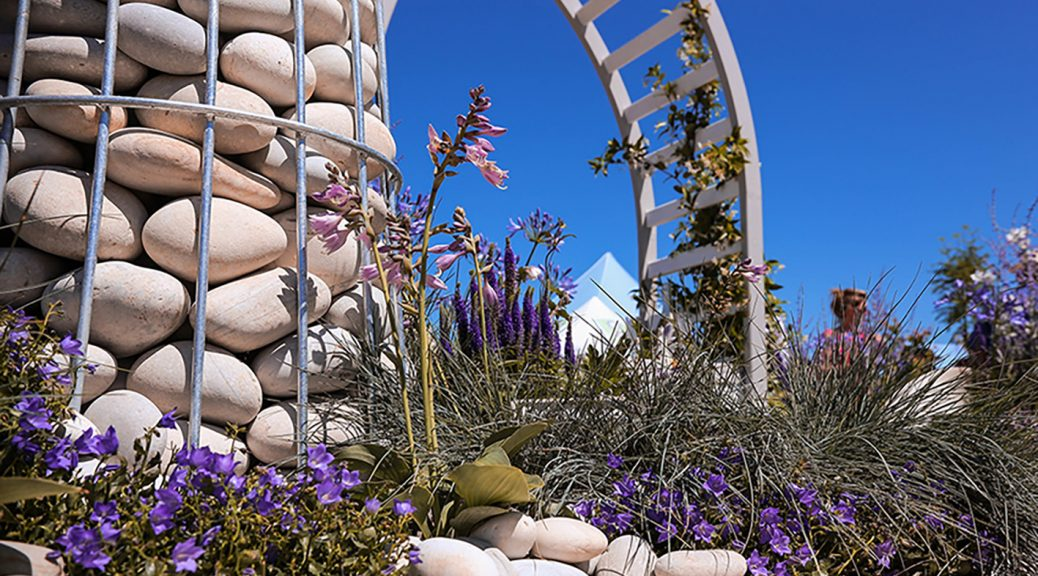 Pastel grey, blue, white cobbles in a steel framed lighthouse in a show garden with purple and green plants.
