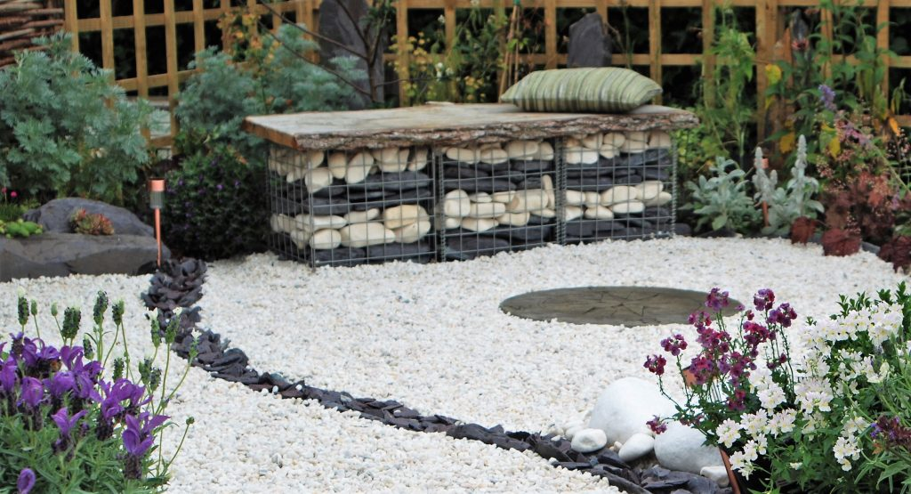 Gabion basket filled with stone to create a bench with a wooden top and green cushion.
