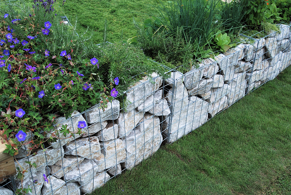Gabion basket filled with a grey rockery stone to create a wall