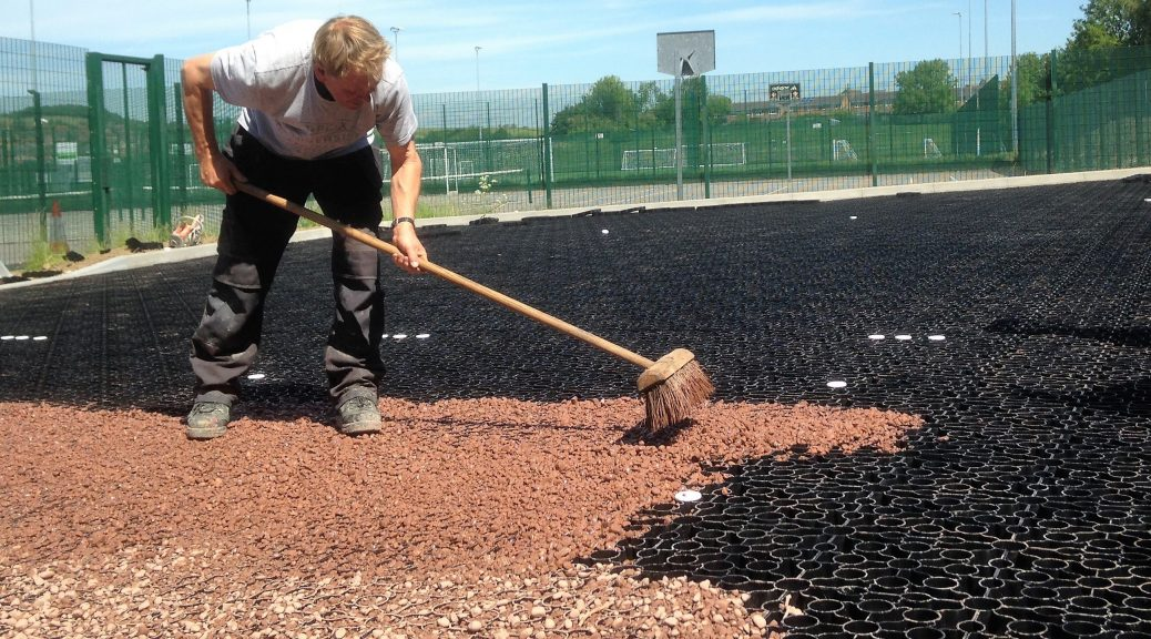 Red gravel being brushed into the gravel grid