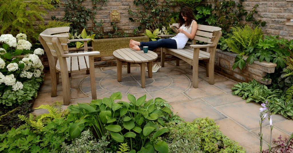 Woman relaxing on a bench with feet resting on a table in front of her. A brown patio is beneath her with lots of plants around.