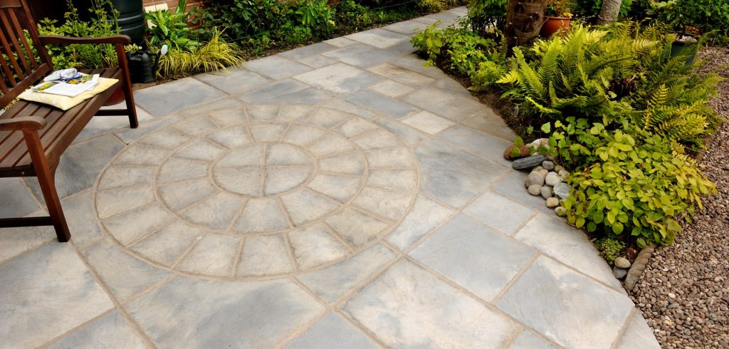 Grey paving circle surrounded by plants and gravel.