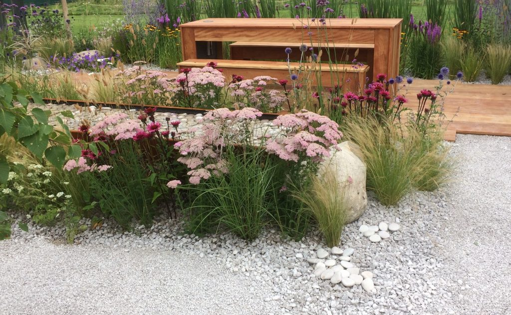 Bench behind a trough water feature filled with white cobbles with different colour flowers around and grey gravel.