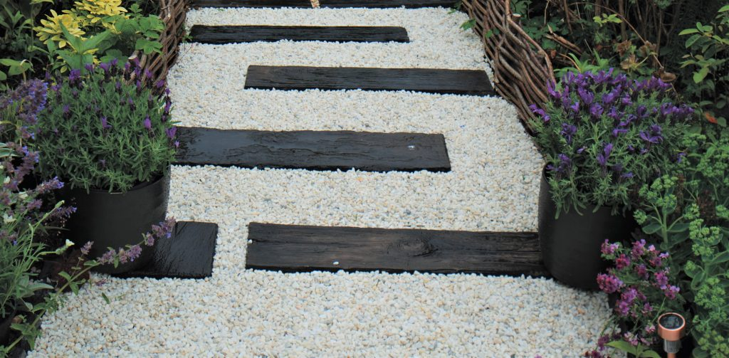 White chippings with concrete wood effect sleepers and flowers lining the sides.