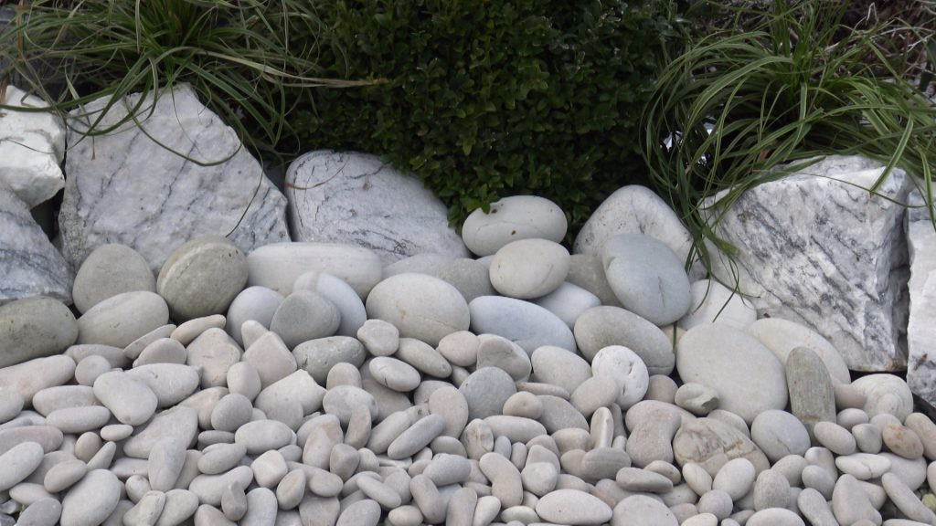Beige duck egg pebbles and cobbles with lilac rockery and a green bush behind.