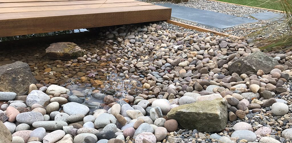 Top 5 garden ideas from Harrogate, wildlife friendly ponds. Water feature made out of brown, red and grey pebbles and cobbles.