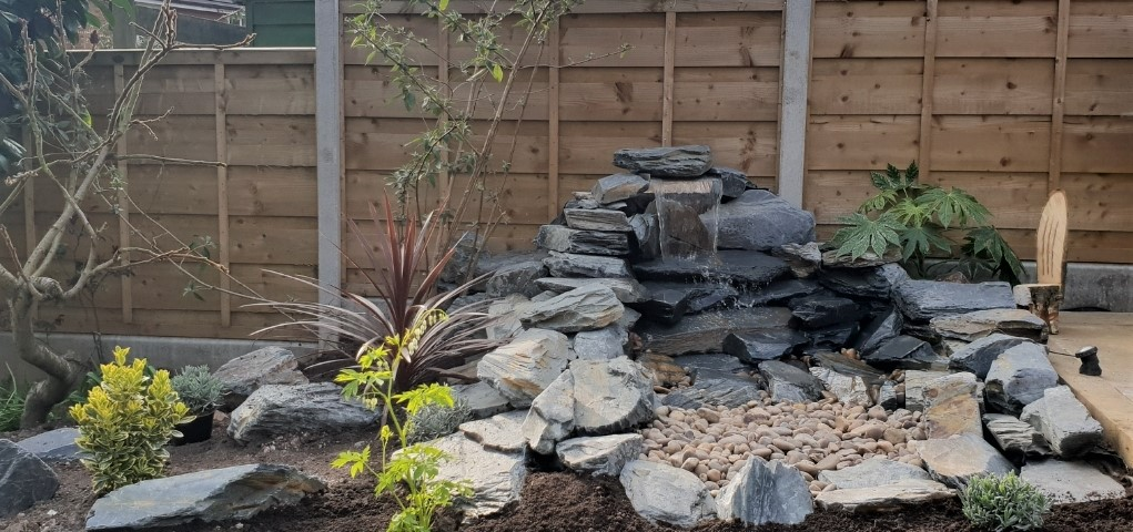 Charcoal Slate Rockery used in a water feature. with Beige pebbles.