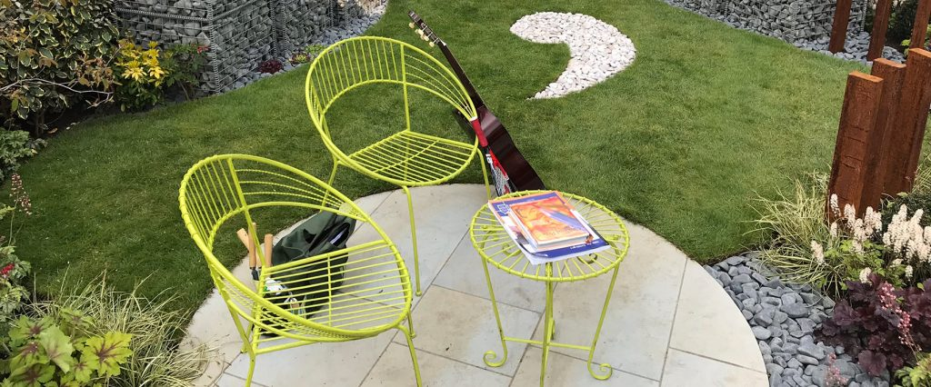 A circular buff patio with green table and chairs with a guitar,