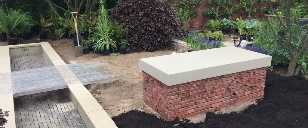 Cande Moortel red and blue brick pond and bench before planting at RHS Chatsworth
