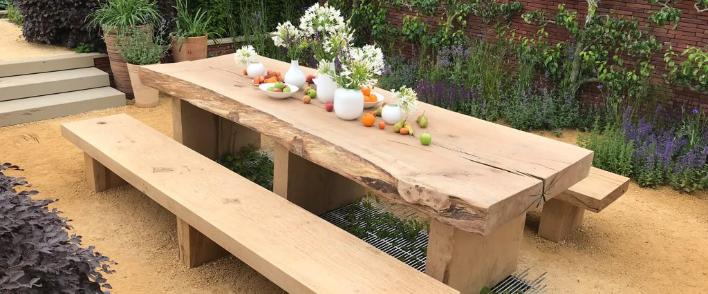 A wooden bench and table set in the Wedgwood Garden at RHS Chatsworth surrounded by brightly coloured plants.