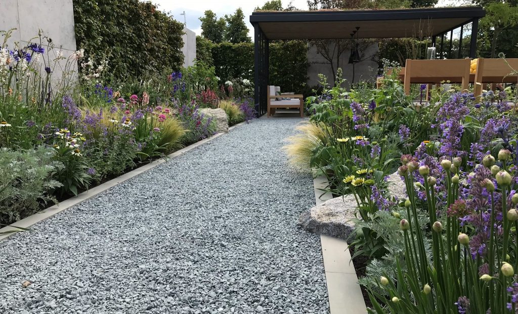 Viking Cruises Lagom Garden with blue/black chippings and purple and green planting.