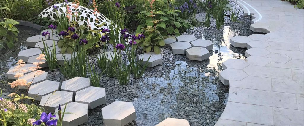 Water feature in garden featuring our Ice Blue Pebbles and grey honeycomb stepping stones.