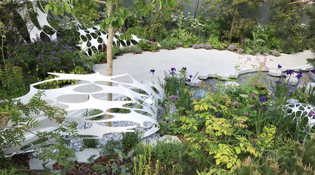 The Manchester Garden at RHS Chelsea with lots of greenery, grey paving and a white woven sculpture.