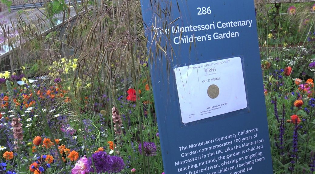 Information plinth with gold medal on in front of The Montessori garden at Chelsea with colourful flowers in the back ground.