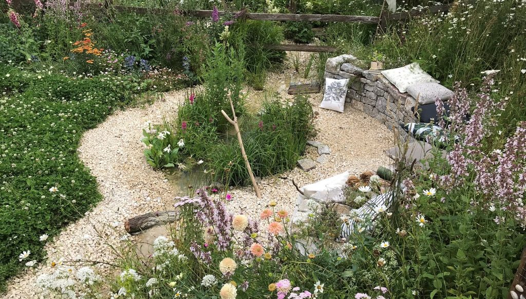 Dry stone bench with cotswold chippings in front of it and central small pond surrounded by wild flowers.