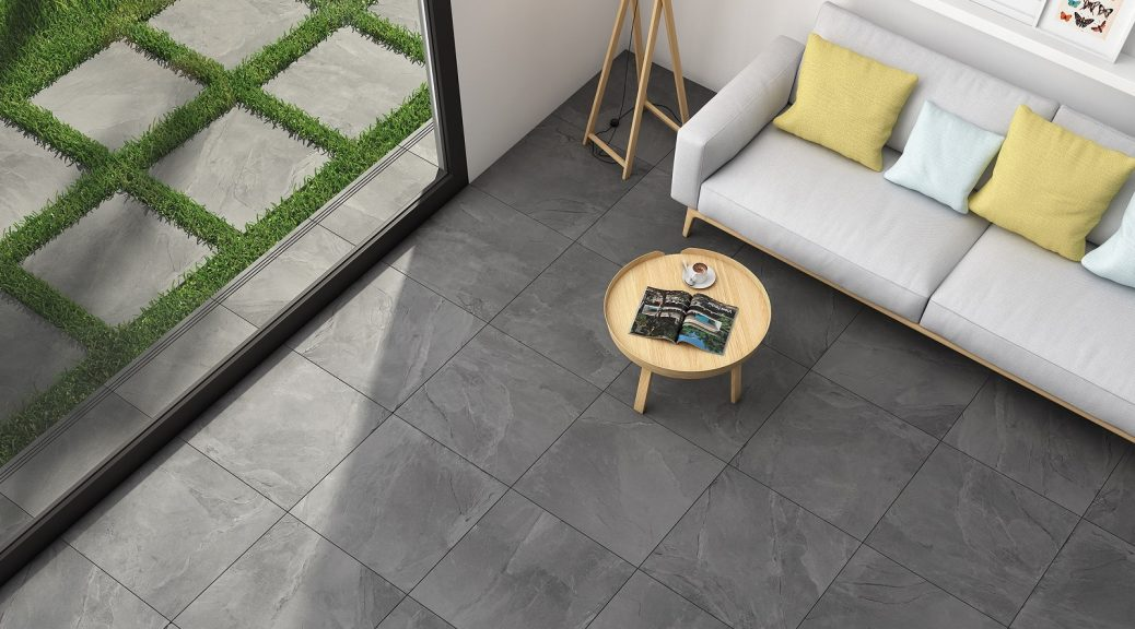 Grey paving slabs underneath a cream sofa with round wooden table.