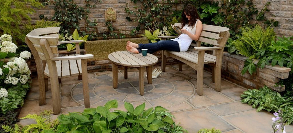 Patio with brown colour tones with wooden table and benches and a woman relaxing and reading a magazine.