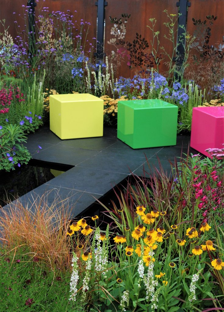 A garden at a flower show that has 3 colourful cubes for seating and a black paving leading up to them. The planting is red, yellow and green to match the colour of the cubes.