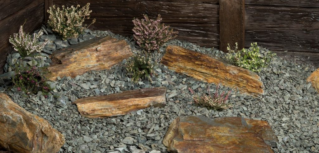 Several pieces of rustic slate rockery  surrounded by green slate chippings and complementary plants.