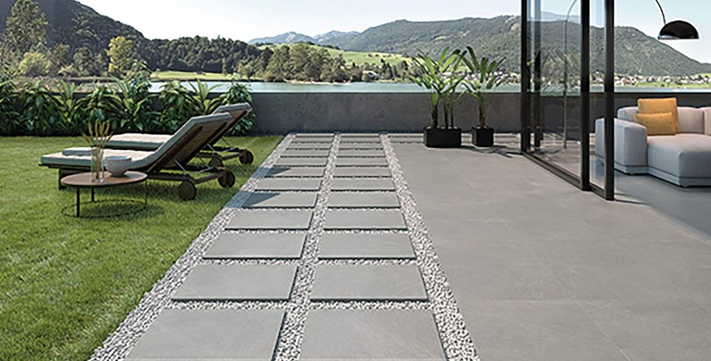 Grey porcelain paving slabs outside next to a grassy area an deck chairs with a view of the mountains.