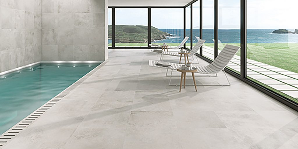 Creamy coloured porcelain paving next to an indoor swimming pool will deck chairs surrounding it.