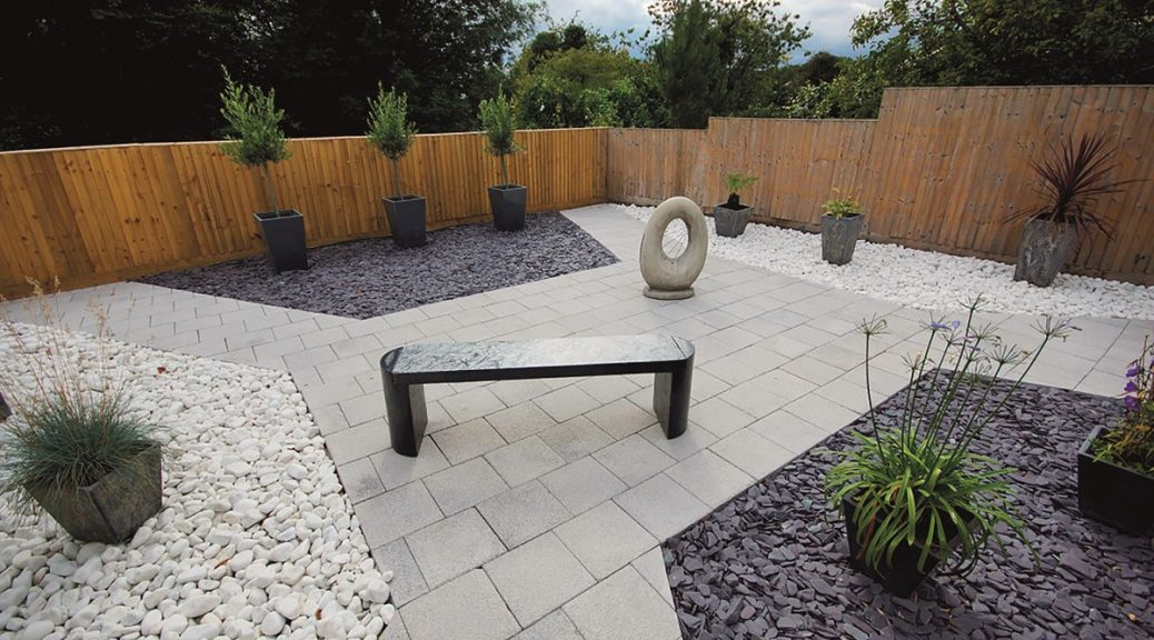 Garden with pale grey paving and white cobbles along with p[um slate paddlestones