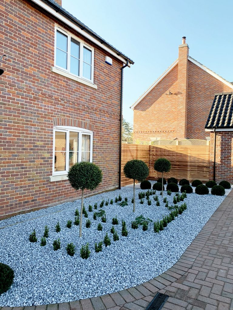 Front border to house with Ice Blue marble chippings and evergreen plants and trees.