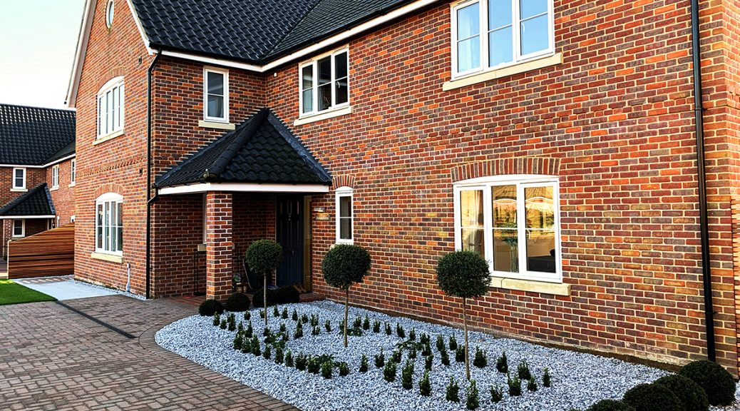 Red brick house with Ice Blue Chippings border at the front and evergreen plants dotted around.
