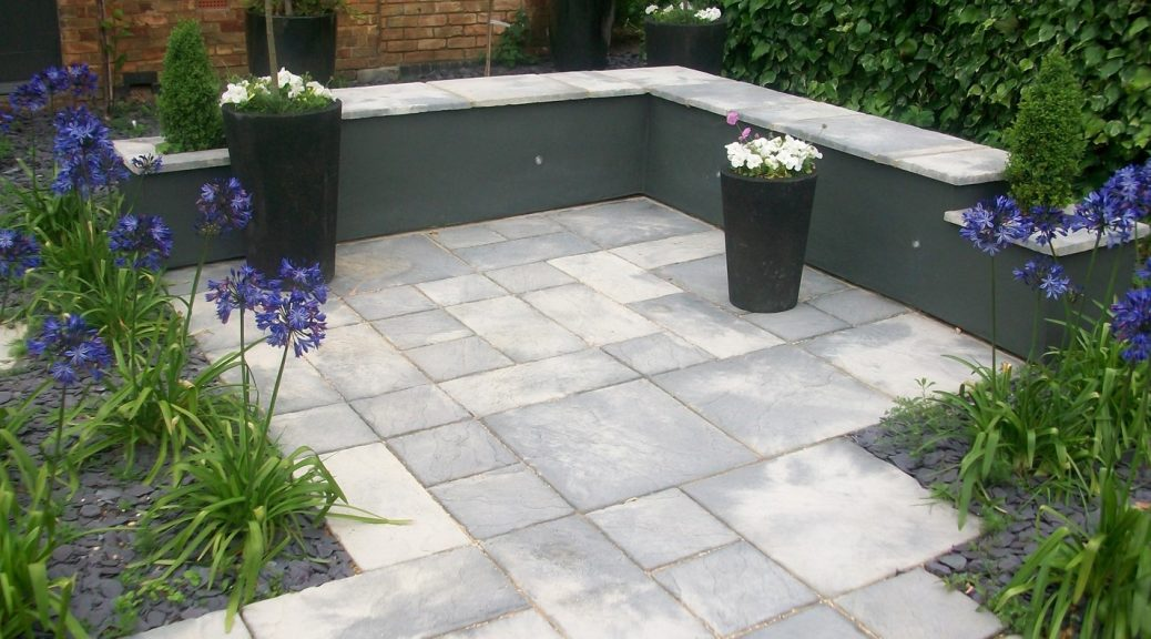 Garden with Bronte Weathered stone paving surrounded by a grey wall.