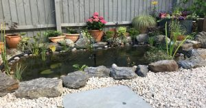 Pond surrounded by grey boulders and plant pots with Cotswold gravel at the forefront.