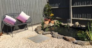 Pond surrounded by Cotswold gravel with a seating area next to it. Terracotta pots decorate the corner.