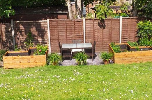 Community garden with seating area surrounded by grass. Featuring raised wooden beds and slate chippings