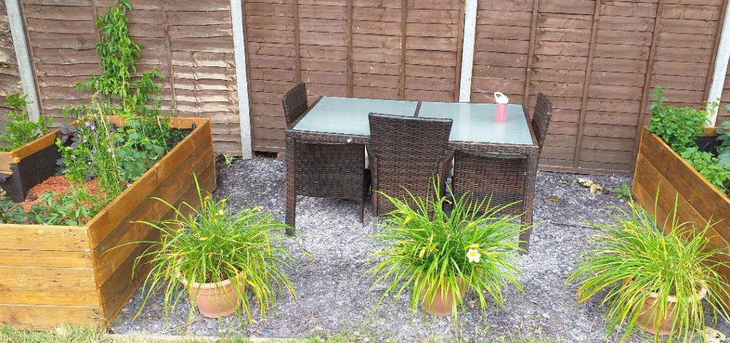 The finished garden including the slate, table and chairs, raised wooden beds and plants in pots.