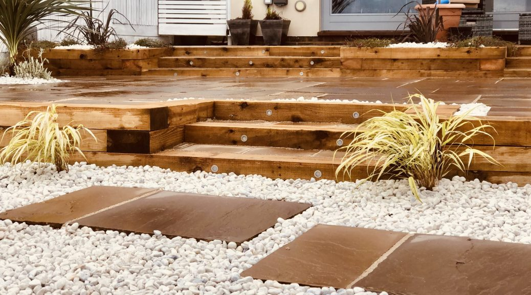 A beach themed garden with steps leading to raised area. all made out of wood. White pebbles in the forefront with patio slabs as stepping stones around them.
