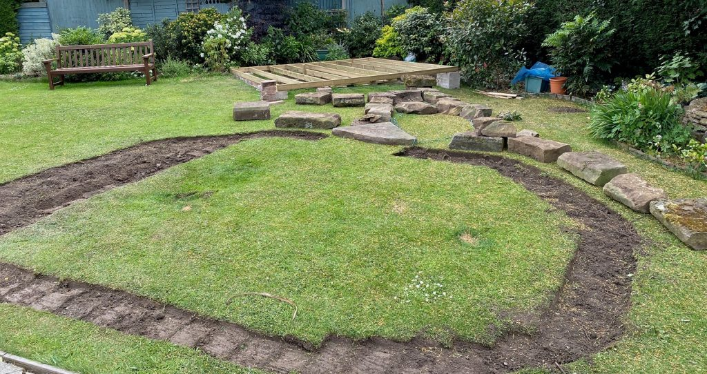 The outline of a garden pond into a grass area with some York Stone rockery pieces around it.