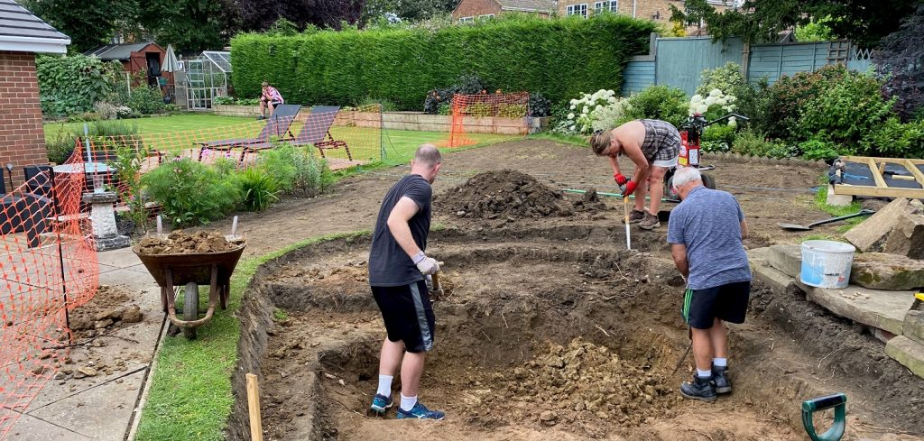 3 people digging out the pond area.