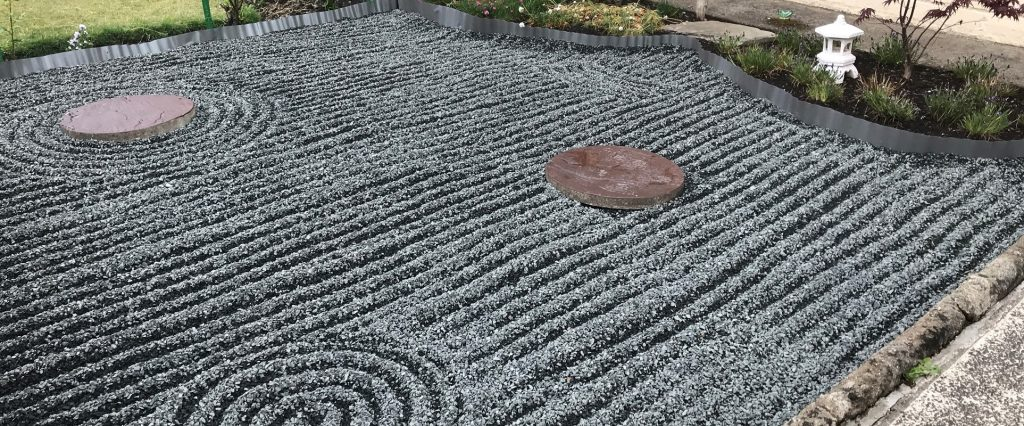 Black basalt gravel racked into rows in a Japanese style garden.
