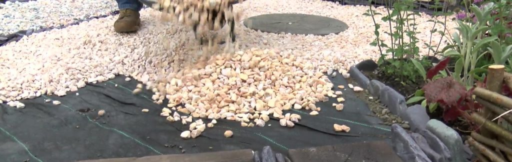 Onyx Gravel chippings being put onto a weed membrane