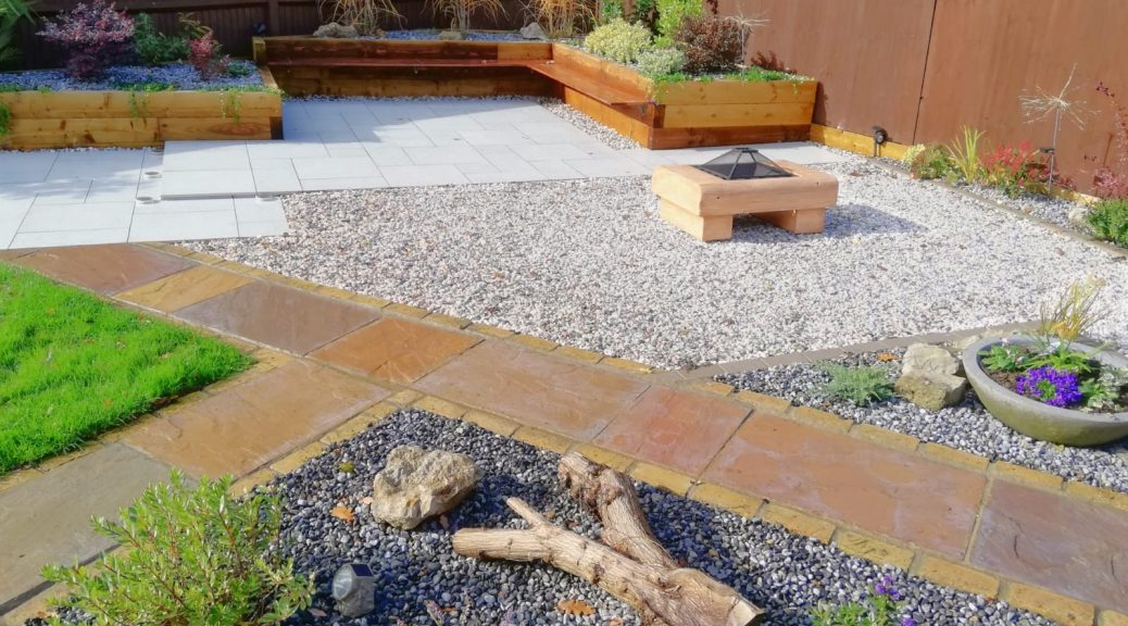 The garden with porcelain paving surrounded by Flamingo Gravel. Ocean Blue Pebbles in the raised beds.