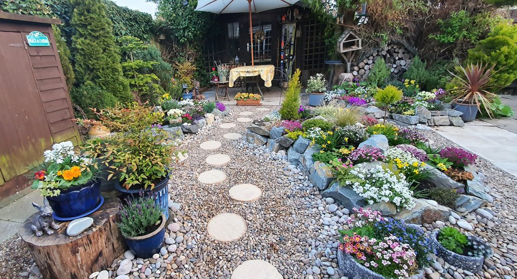 completed rockery garden with blue pots and flowers in full bloom