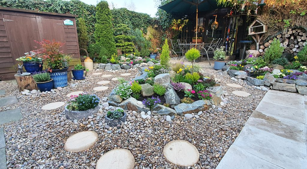 completed rockery garden with golden gravel, rounded stepping stones and pebbles