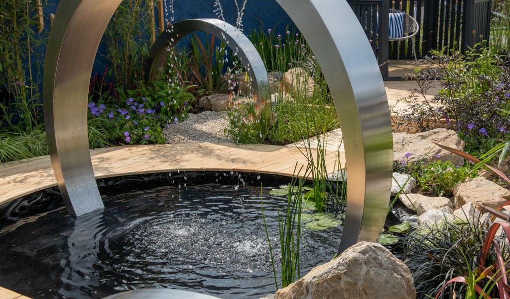 Petrus: Full Circle garden with large silver circle water feature and boulders around a pond.