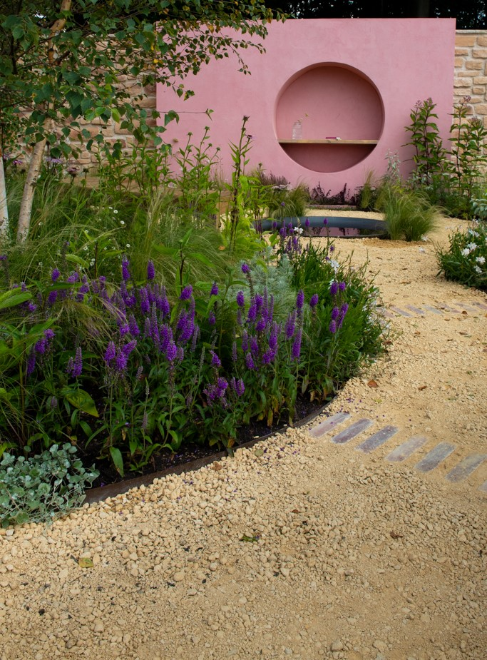Dreamscape Garden at RHS Tatton Park Flower Show. Goldpath self binding gravel forms the pathway leading up to a pink sculptural wall..