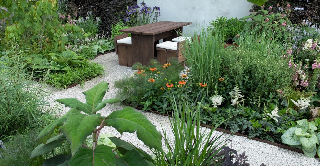 The Earth Garden with wooden bench and lush green planting surrounding it.
