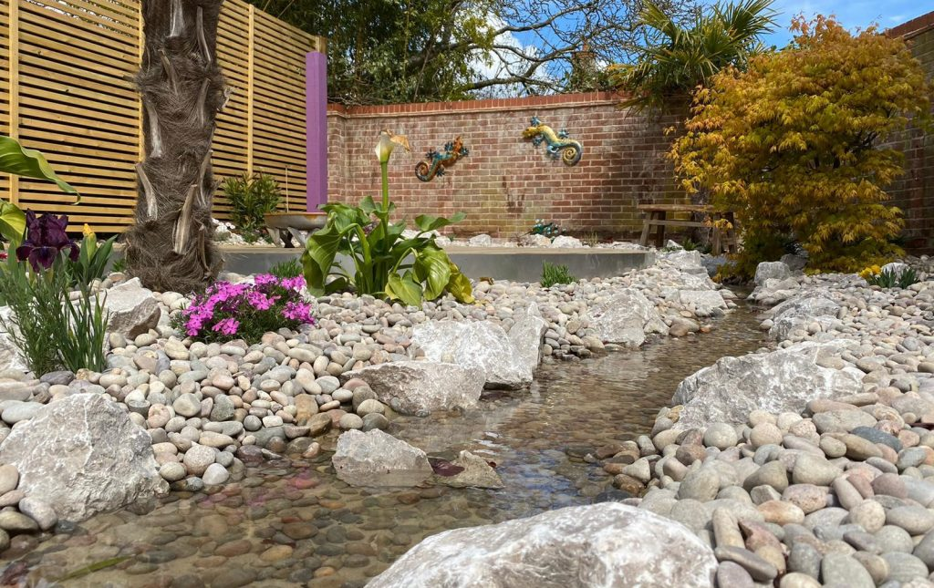Longstone Rockery Stone with Scottish Pebbles. These line the river water feature in the garden.